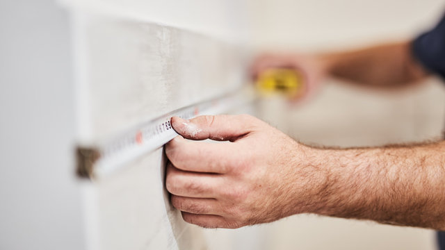 Worksman using tape measure for home renovation.