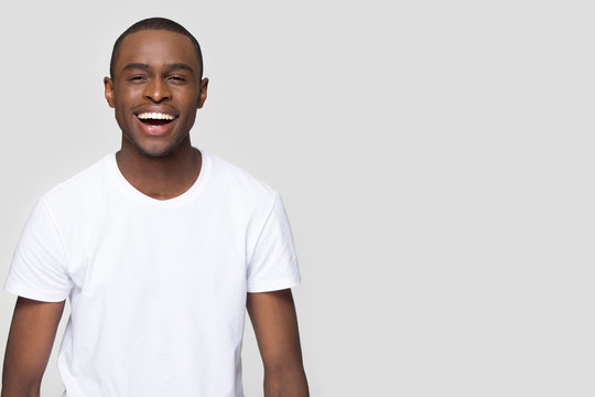 African man laughing looking at camera isolated on grey blank