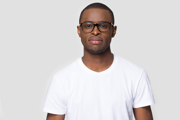 Serious african male wearing glasses white t-shirt posing indoors
