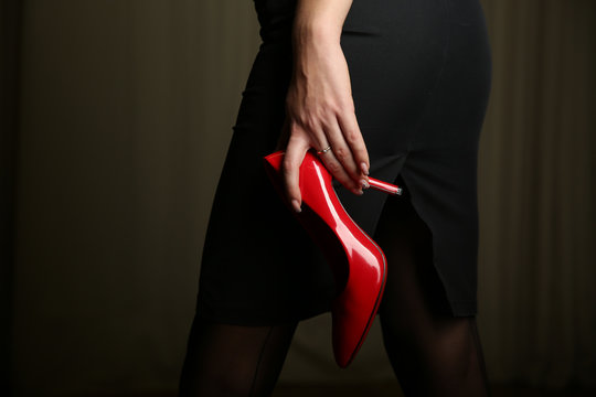 a woman's hand holding a red shoe close-up. the girl carrying a red elegance shoe in her hand close-up
