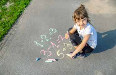 The child decides grunts on the asphalt. Selective focus.
