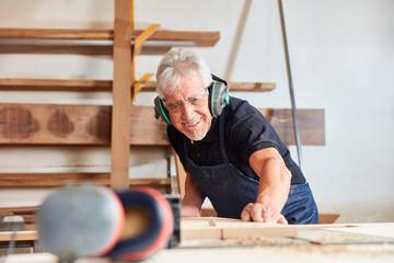 Alter Tischler sägt Holz an der Kreissäge