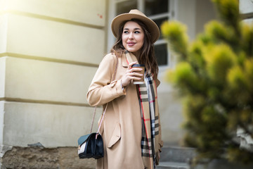 Cheerful young woman in the street drinking morning coffee