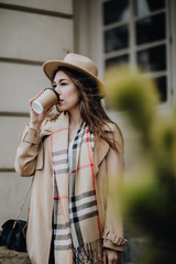 Happy woman holding coffee to go while walking in city street in autumn day
