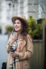 Young pretty woman standing at the street drinking coffee to go and using mobile phone