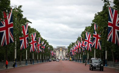 A London taxi makes its way down the Mall, decked out in Union flag, with Buckingham Palace in the background in London