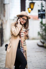 Happy young woman with headphones talking on the mobile phone in the city