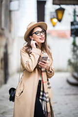 Young woman using mobile phone and talks via earphone headset while standing outdoor in the street