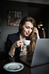 Portrait of a young beautiful businesswomen enjoying coffee during work on portable laptop.