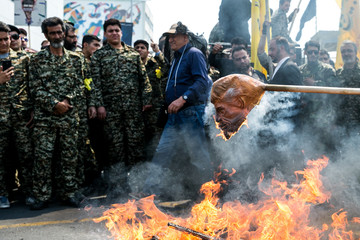 Iranians burn a mask of  U.S. President Donald Trump during a protest marking the annual al-Quds Day (Jerusalem Day) on the last Friday of the holy month of Ramadan in Tehran
