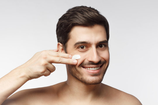 Smiling shirtless young man applying facial cream, isolated on gray background. Skin care concept