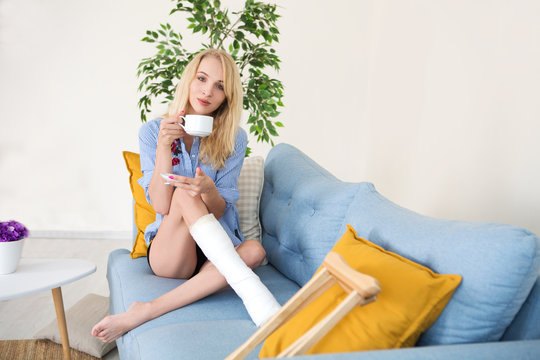 Young woman with crutch and broken leg in cast drinking tea sitting on sofa at home