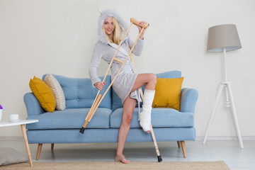 Cheerful playful young woman in a dressing gown having fun with crutch in the room