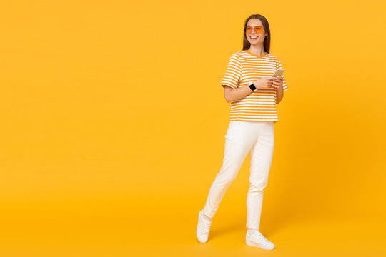 Young woman walking and communicating via phone, isolated on yellow background with copy space on left