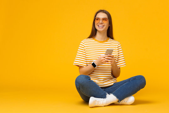 Happy young girl sitting on the floor, holding smartphone in hands and looking away, isolated on yellow background with copy space