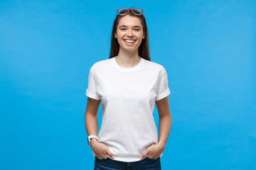 Fototapeta Young female standing with hands in pockets, wearing blank white t-shirt with copy space, isolated on blue background obraz