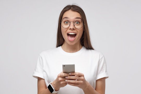 Wow! Close-up shot of young girl in white t-shirt, holding smartphone, looking surprised and shocked, isolated on gray background.