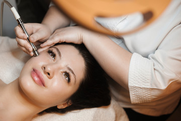 Upper view portrait of a beautiful caucasian female leaning on a bed with eyes open while having non invasive microdermabrasion on her face in a spa salon.