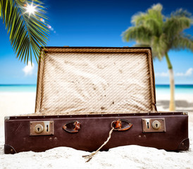 Summer suitcase on sand and beach landscape with palm and ocean. Free space for your decoration.