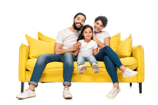 happy latin parents smiling while sitting on sofa with adorable daughter isolated on white