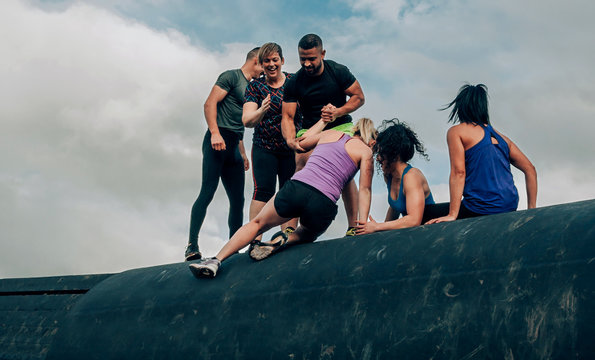 Group of participants in an obstacle course climbing a drum