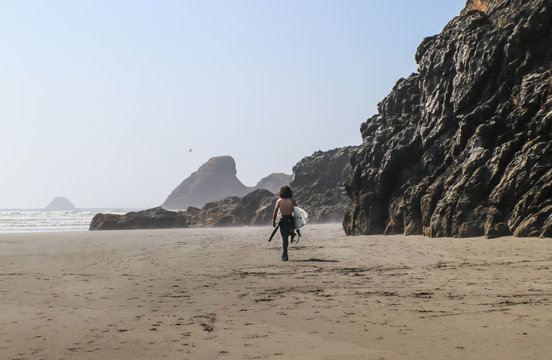 Young man surfer with no shirt and bushy long dark hair walks down misty beach with towering wet rock cliffs toward ocean with waves rolling in - shades of brown and selective focus