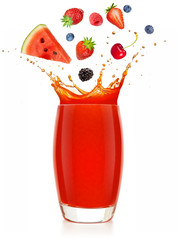 Wall Mural - red fruits falling into a splashing glass of juice isolated on white background