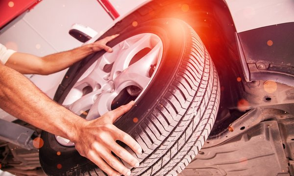 Male hands with Automobile tires on background