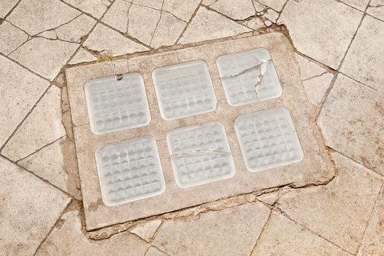 Ein Lichtschacht mit Glasbausteinen in einem Weg mit zerbrochenen Platten aus Beton