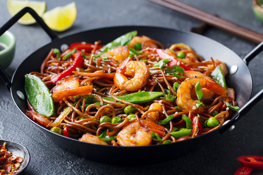 Stir fry noodles with vegetables and shrimps in black iron pan. Slate background. Close up.