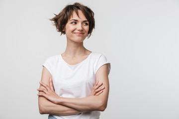 Image of optimistic woman in basic t-shirt smiling and looking aside while standing with arms crossed