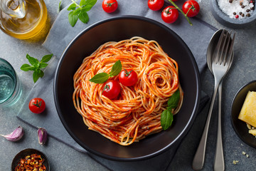 Pasta, spaghetti with tomato sauce in black bowl on grey stone background. Top view.