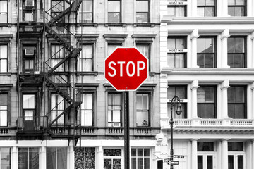 Red stop sign against background of old black and white buildings in SoHo Manhattan, New York City