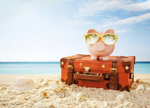 Piggy bank wearing sunglasses resting on the tropical beach with copy space