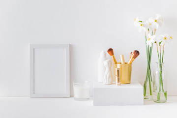 Home interior with decor elements. White frame, white daffodils in a vase, cosmetic set
