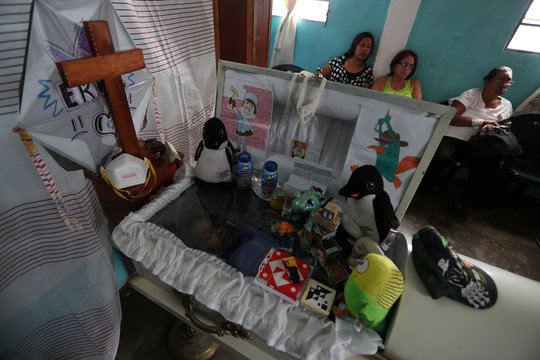 The open coffin of Erick Altuve, a 11-year-old boy who died from respiratory problems while in care for stomach cancer at the public Jose Manuel de los Rios hospital, is seen during his wake at Petare neighborhood in Caracas