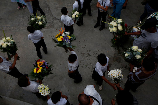School mates of Erick Altuve, a 11-year-old boy who died from respiratory problems while in care for stomach cancer at the public Jose Manuel de los Rios hospital, hold up flowers near his casket at Petare neighborhood in Caracas