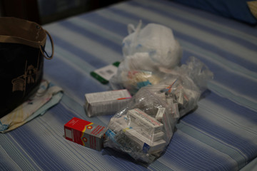 A plastic bag containing medicines of Mariana Navas, a six-year-old girl who is in care at the public Jose Manuel de los Rios hospital for leukemia, is seen on a bed at her family flat, at 'Los Bosques del Silencio' neighborhood in Caracas