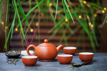 Green tea in tea pot and chawan bowls, cups. Outdoor background with bamboo leaves and bokeh lights. Copy space.