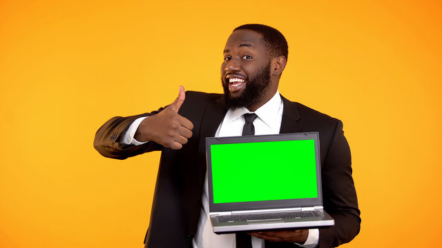 Happy smiling afro-american male showing prekeyed laptop and thumbs-up gesture