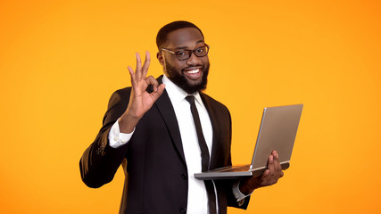 Happy handsome black male in suit holding laptop and showing ok gesture, success