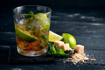 Cocktail with black rum, lime and mint, Brazilian Сaipirinha alcoholic drink on dark wood