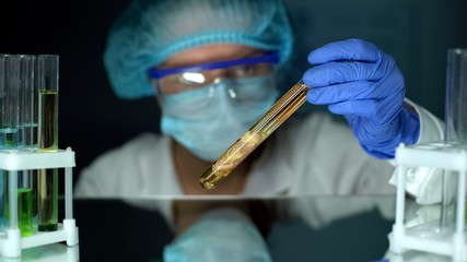 Microbiologist studying tissue sample in preservative agent, decomposition speed Wall mural