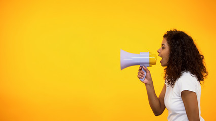 Afro-American girl screaming in megaphone, spreading information, awareness