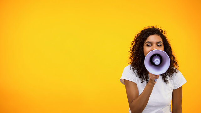 Afro-American female shouting in megaphone, public relations, social opinion