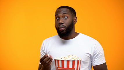 Excited African-American male with popcorn watching interesting TV program Wall mural
