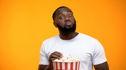 African-American male with popcorn watching science TV show, new knowledge Fototapete