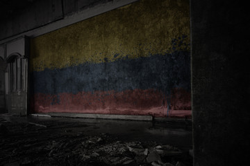 painted flag of colombia on the dirty old wall in an abandoned ruined house