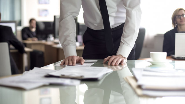 Businessman studying contract, office employees working on background, busy life