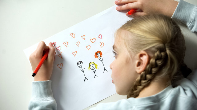 Little girl painting family with heart signs, orphan dreaming about parents